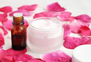 Jar of soft pinkish skin care cream, fragrance, bright pink fresh rose petals moistuned. Gorgeous aroma body care spa.